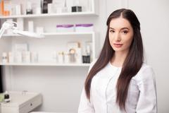 Attractive female expert beautician is waiting for customer - stock photo