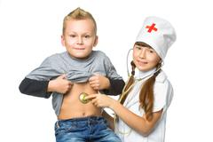 Smiling girl doctor with stethoscope in uniform diagnoses boy isolated on a - stock photo