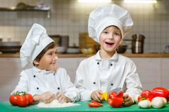 Funny happy chef boys cooking at restaurant kitchen - stock photo