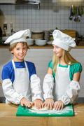 Funny happy chef boy width girl cooking at restaurant kitchen and rolls the - stock photo