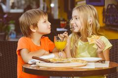 Happy or satisfied boy width girl eating pizza and drinking juice - stock photo