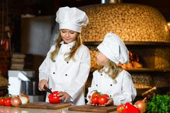 Smiling Chef girls preparing healthy food vegetable salad at restaurant kitchen - stock photo