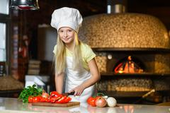 Smiling Chef girl preparing healthy food vegetable salad at restaurant kitchen - stock photo