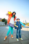 Smiling woman width boy holding color plastic penny board skateboard at city Stock Photos