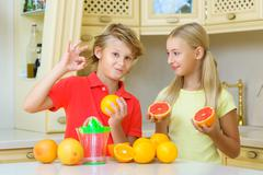 Children with citrus. boy showing ok close girl holding a grapefruit - stock photo