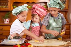 two little chefs enjoying in the kitchen making big mess - stock photo