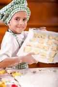 young boy chief shows prepared cookies for baking - stock photo