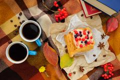 Romantic autumn still life with blanket, cake, book, coffee cups and leaves, top - stock photo