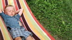 Little Boy enjoys free time  in hammock Stock Footage