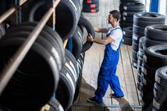 Auto mechanic  choose tire for car - stock photo