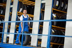 smiling auto mechanic has sold a car tire - stock photo