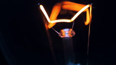 The filament incandescent lamp is lighting and moves on a black background - stock footage
