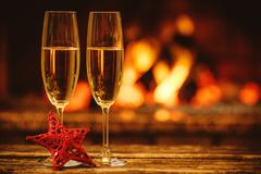 Two glasses of sparkling champagne in front of warm fireplace. C - stock photo