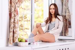 Beautiful young lady is sitting on the windowsill Stock Photos