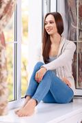 Beautiful young lady on the windowsill Stock Photos