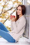 Woman on the windowsill with a cup of drink Stock Photos