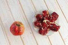 juicy lobules of garnet on plate - stock photo