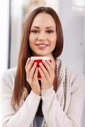 Attractive young lady with a cup of drink Stock Photos