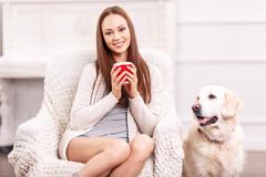 Pretty girl in the armchair with her pet around Stock Photos