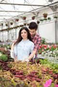 Happy couple in greenhouse with flowers Stock Photos