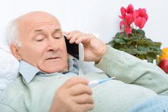 Despondent weary aged man calls up his relatives Stock Photos