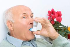 Senior aged man uses inhaler to cure his ache Stock Photos