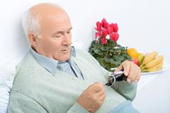 Senior aged man pours himself cough syrup Stock Photos