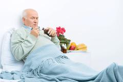 Elderly man rests in bed and pours cough syrup Stock Photos