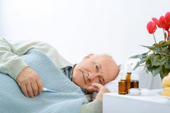 Senior aged man is resting while holding a thermometer - stock photo