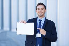 Smiling reporter points at sheet of paper Stock Photos