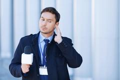Journalist checks his gadgets before broadcast - stock photo