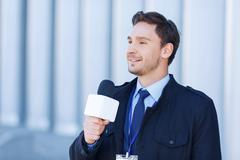 Journalist smiles while recording a newscast Stock Photos