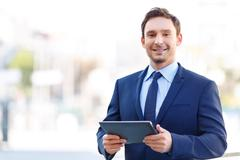 Grinning gentleman on balcony holding a tablet - stock photo