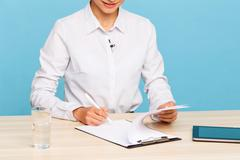 Pleasant TV announcer making notes - stock photo