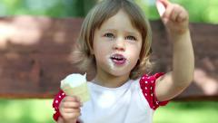 Beautiful girlie sits on the bench and eats ice cream Stock Footage