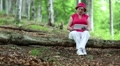 Woman sits on a fallen tree in the forest and uses tablet PC HD Footage