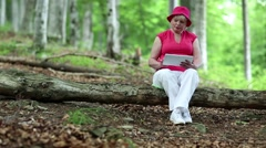 Woman sits on a fallen tree in the forest and uses tablet PC Stock Footage