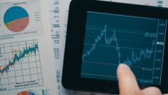 Trader moving graphics currency quotes on the screen of the tablet Stock Footage