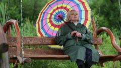 Woman in green raincoat and with umbrella sits on the swing bench Stock Footage
