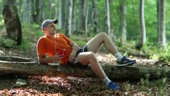Man with red smartphone lies on a fallen tree in forest and listens to music Stock Footage