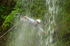 Canyoning Tour Leader Jumping Into A Waterfall Stock Photos