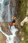 Stock Photo of Rappelling Tall Canyon Waterfall