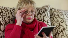 Senior woman sits on a sofa and uses electronic book. Woman with e-book Stock Footage
