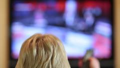 Woman with remote control switching tv channels Stock Footage