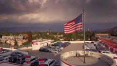 Aerial view of US flag waving on top of Toyota of North Hollywood car dealership - stock footage