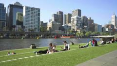 People relaxing on the riverbank in a city - stock footage
