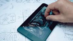 Engineer considers the image of a mechanical device on the screen of the tablet Stock Footage