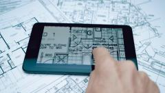 Architect moves his finger on the touchpad of the structure of the building plan Stock Footage