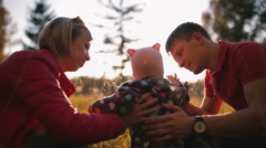 Happy parents talk with the baby in the autumn field. Stock Footage