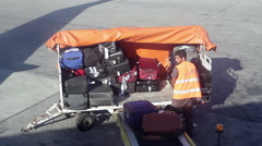 Airport ground crew takes luggage out of airplane from the hold - stock footage